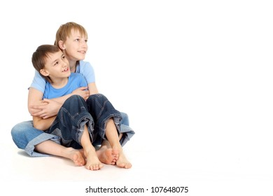 Two boys sit on the floor and look to the side on a white background