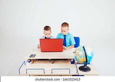 two boys sitting at the computer school