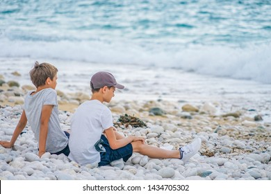Two boys sitting next to each other on the beach by the sea