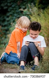 Two boys sitting on the grass in the park playing a game on their smart phone