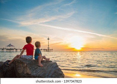 Two boys sitting on the rock at the beach watching beautiful sunset, South Australia