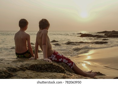 two boys sitting on a rock on beach near sea and watching the sun. andaman sea, Phuket island, Thailand, summer time