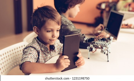 Two Boys Sitting at Table and Programming Robot. Young Boy in Shirt. Indoor Joy. Modern Hobby Concept. Modern Technology. Robot Engineering Concept. Teenager with Robor. Innovation for Fun.