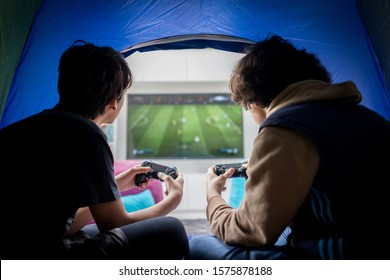 Two boys sitting in tent playing video games on game console