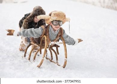 Two boys sledding with mountain warm winter day