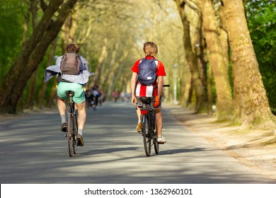 Two boys with small backpacks biking in a sunny Amsterdam Vondelpark in the Netherland.