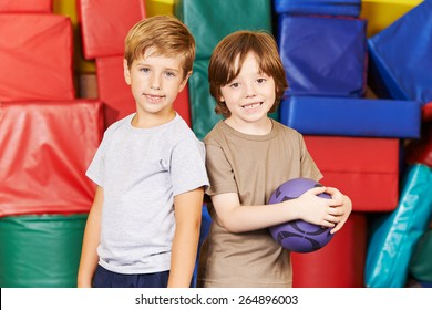Two boys standing with a ball in gym of a preschool