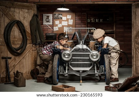 Two boys standing at the mechanic with tools retro car near the garage