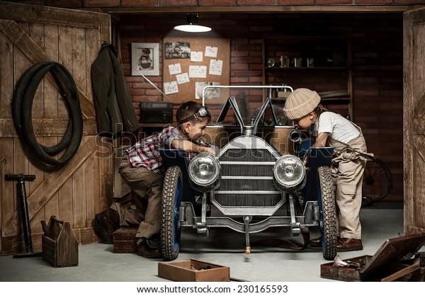 Zwei Jungen stehen am Mechaniker mit Werkzeugen Retro-Auto in der Nähe der Garage