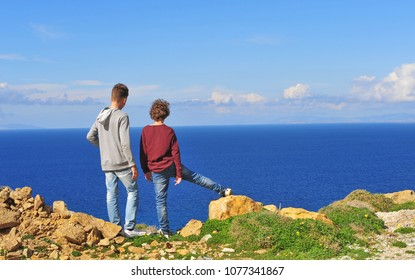 Two boys standing on cliffs by the sea, Greece