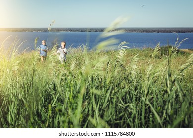 Two boys in striped t-shirts running on the field. Summer leisure and friendship concept.