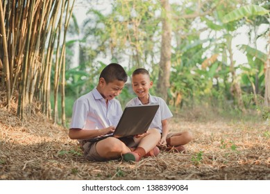 Two boys studying by online learning with laptop at outdoor.