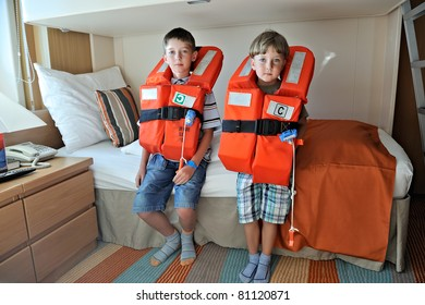 two boys testing their orange life jackets in the cabin of a line cruiser