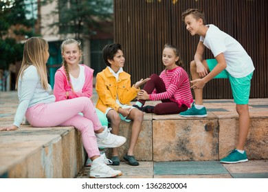 Two boys and three girls are talking about play on walk in the park.