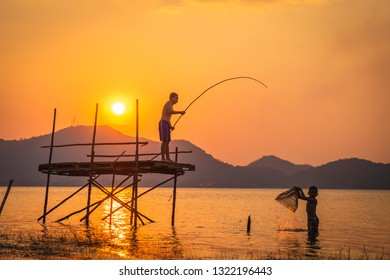 Two boys use fishhook and basket to catching fish in the lake in the evening with beautiful golden sky