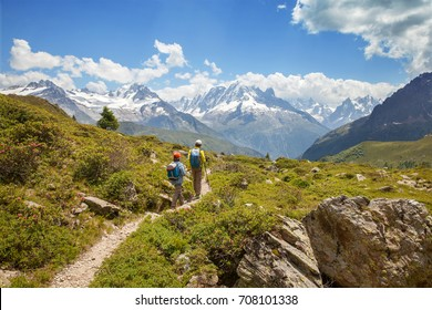 Two boys are walking on mountain path in summer day