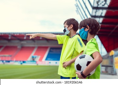 Two boys wanting to play football in stadium during covid-19 wearing face masks