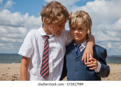 Two boys wearing business suits - best friends hugging on the beach