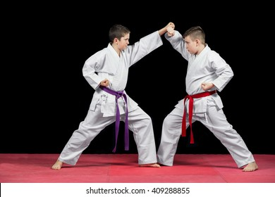 Two boys in white kimono fighting isolated on black background.