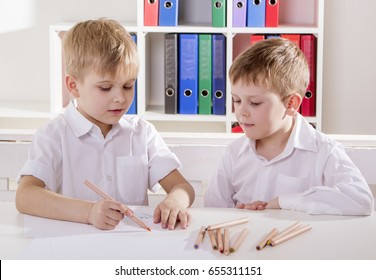 Two boys in white shirts are sitting at a desk and drawing with pencils. Learning process.