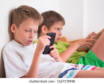 two boys(brothers) playing games on their devices