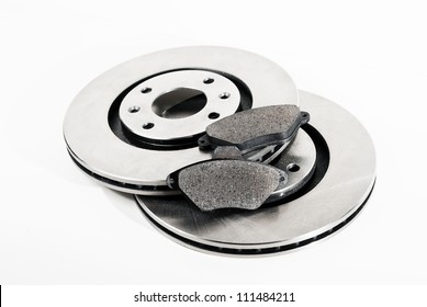 Two brake discs and brake pads isolated on white.