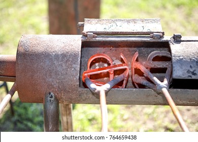 Two branding irons heating in a burner in a field glowing red hot ready to be applied to livestock