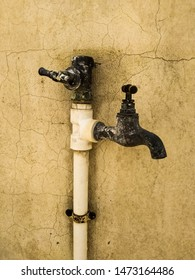 Two brass outdoor wall-mounted rusty water faucets connected to a polyvinyl pipe