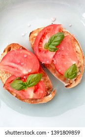 Two bread toasts with tomatoes and basil. Top view, eating healthy. Home made recipe. Easy meal. Breakfast, snack or appetizer. Copy space on top and bottom.