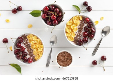 Two breakfast bowls with corn flakes, greek yogurt, sweet cherry and flax seeds on white wooden table. Top view.