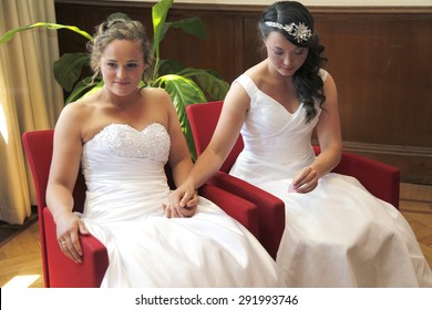 two brides getting married hold hands sitting in red chairs