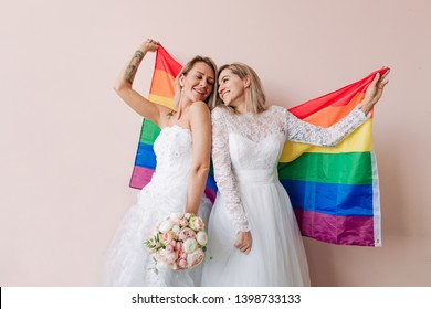 Two brides holding a rainbow flag holding a bouquet of flowers