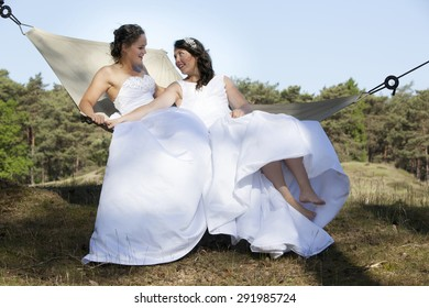 two brides look at each other in hammock against blue sky with forest background