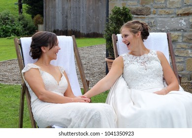 Two brides relaxing on deck chairs after their wedding, smiling at each other in conversation , both happy and wearing white traditional dresses, with their hair up, in the Yorkshire countryside
