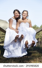 two brides show bare feet in hammock against blue sky with forest background