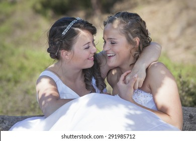 two brides smile and embrace in nature surroundings on sunny day