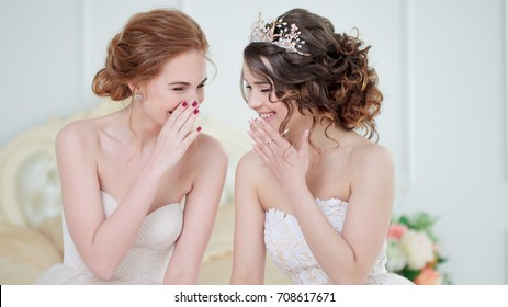 Two brides are whispering about something and laughing. Beautiful delicate Girls in wedding dresses.
