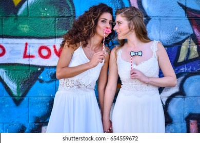 two brides white dress stand at their wedding day at greffiti wall. holding stick