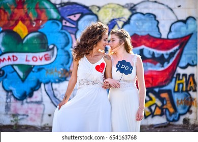two brides white dresses looking one on each other.   in the background Colorful graffiti. one of them holding I DO stick