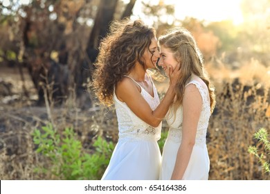 two brides white dresses looking one on each other. close face to face. background at the forest.