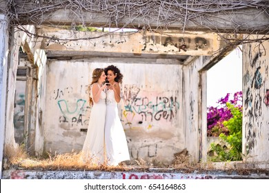 two brides white dresses looking one on each other.   in the background Colorful graffiti. at old broken abandoned house