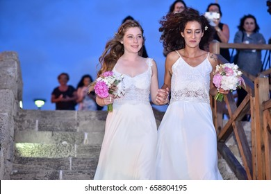 two brides women white dress walk toward the canopy. Holding a Bouquet flowers hand