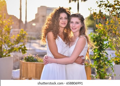 two brides women white dress hugging each other and kissing, at the background street.