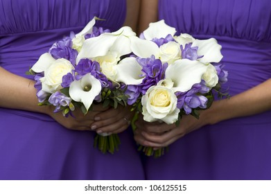 two bridesmaids in purple with wedding bouquet