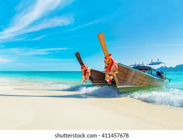 Two bright decorated thai longtail boats at Long Beach (Had Yao beach), best Phi Phi Don island beach, Thailand, view to Phi Phi Lee island silhouette at horizon