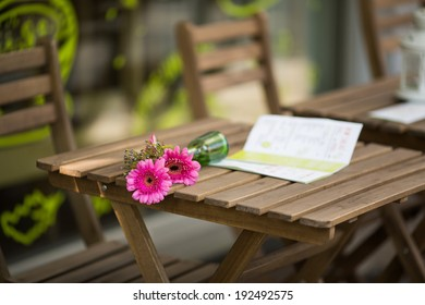 Two bright pink gerbera daisy flowers in overturned vase and menu on the wooden table, failed romantic date scene in the street city cafe, Berlin, Germany