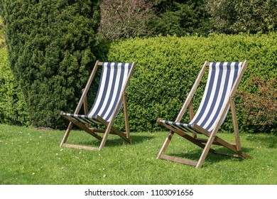 Two british deckchairs with striped cloth in an English garden in summer