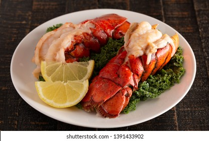 Two Broiled Lobster Tails on a Bed of Kale with Lemon Slices