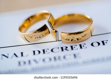 Two broken golden wedding rings divorce decree document. Divorce and separation concept