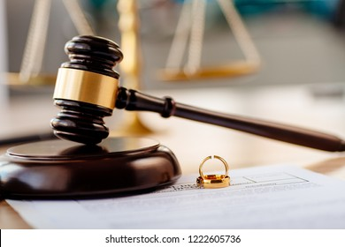 Two broken wedding rings and judge gavel. Divorce, separation and family law concept